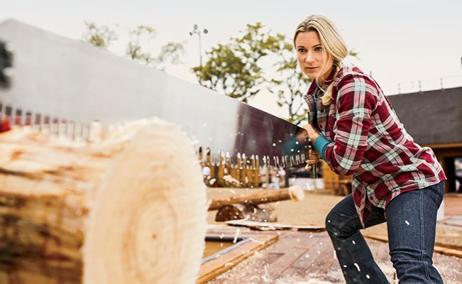 World Champion Lumberjill Shana Martin sawing logs in a Crosscut Flannel Shirt.