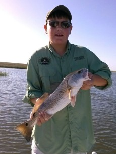 Vanishing Paradise's youngest ambassador Sean Turner holding a speckled trout from the marshes of Louisiana.